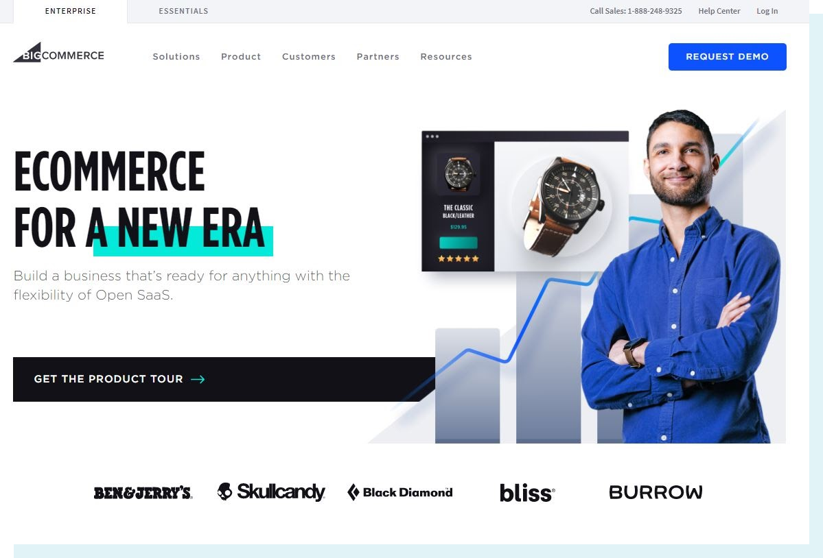 """An image of the BigCommerce homepage. The main text reads """"Ecommerce for a new era,"""" with brands like Ben & Jerry's, Black Diamond, and Skullcandy featured in bold text. There is a man dressed business casual in front of a blue data chart."""